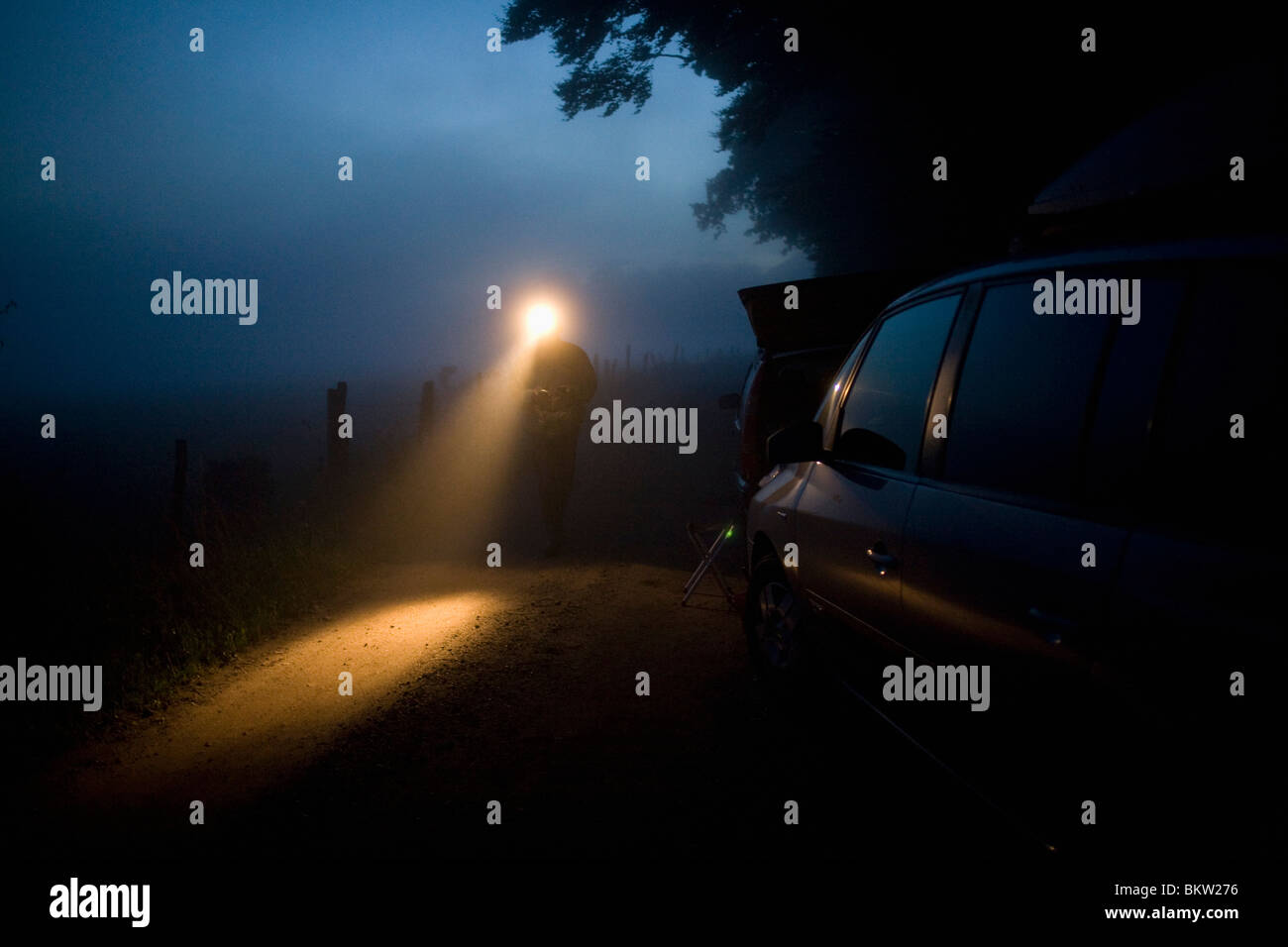 Parked car and man with flashlight - Stock Image