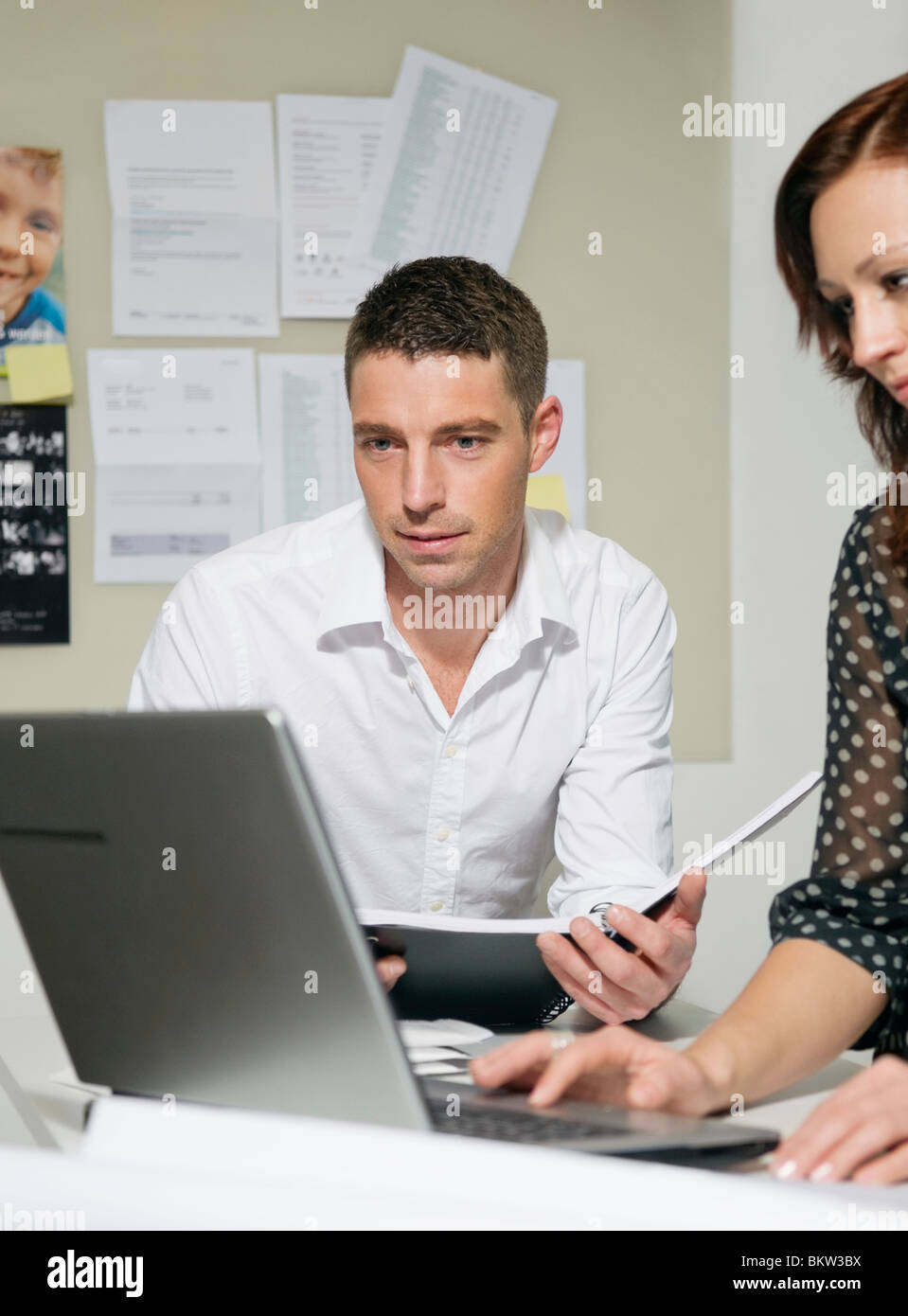 Two people at desk look at computer - Stock Image