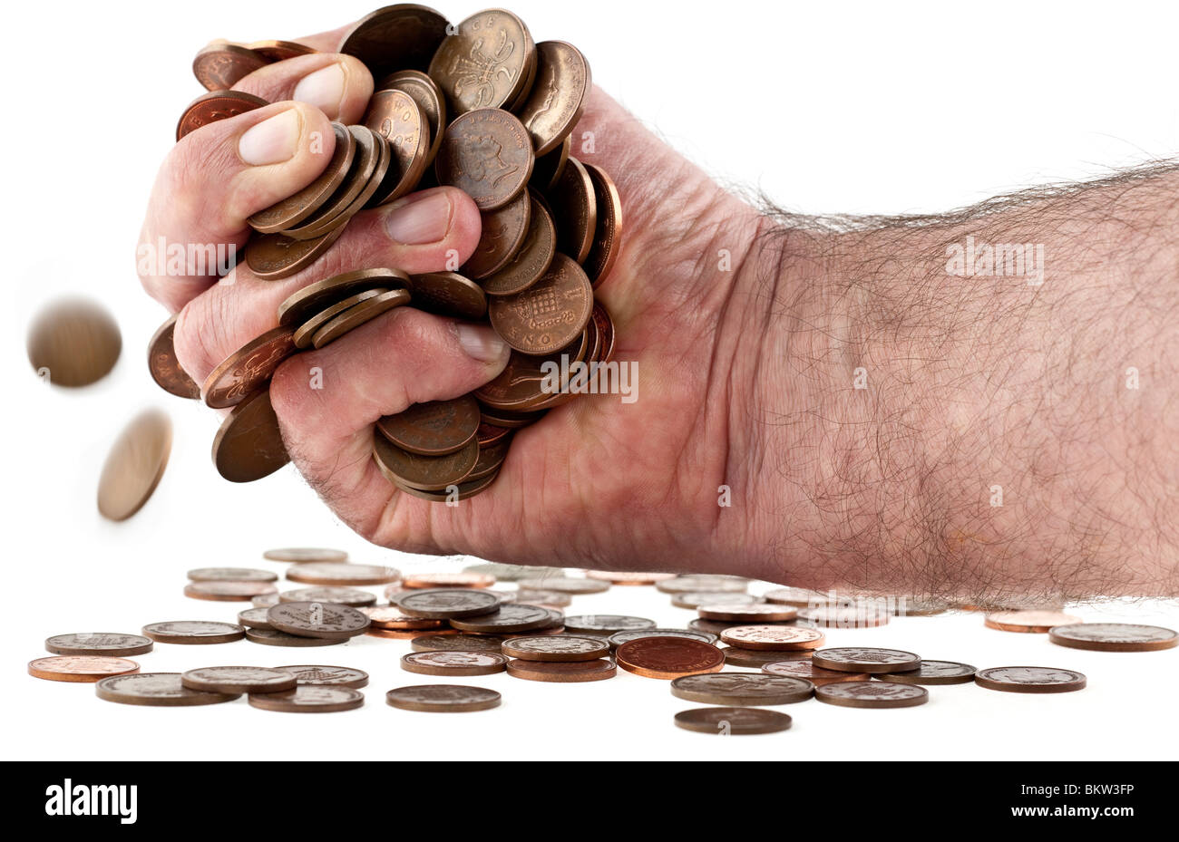 Mans hand stuffed with British currency copper coins - Stock Image