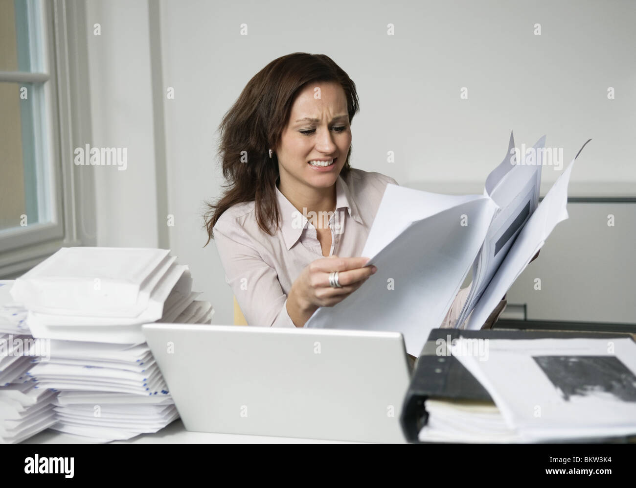 Woman behind piles of paper - Stock Image