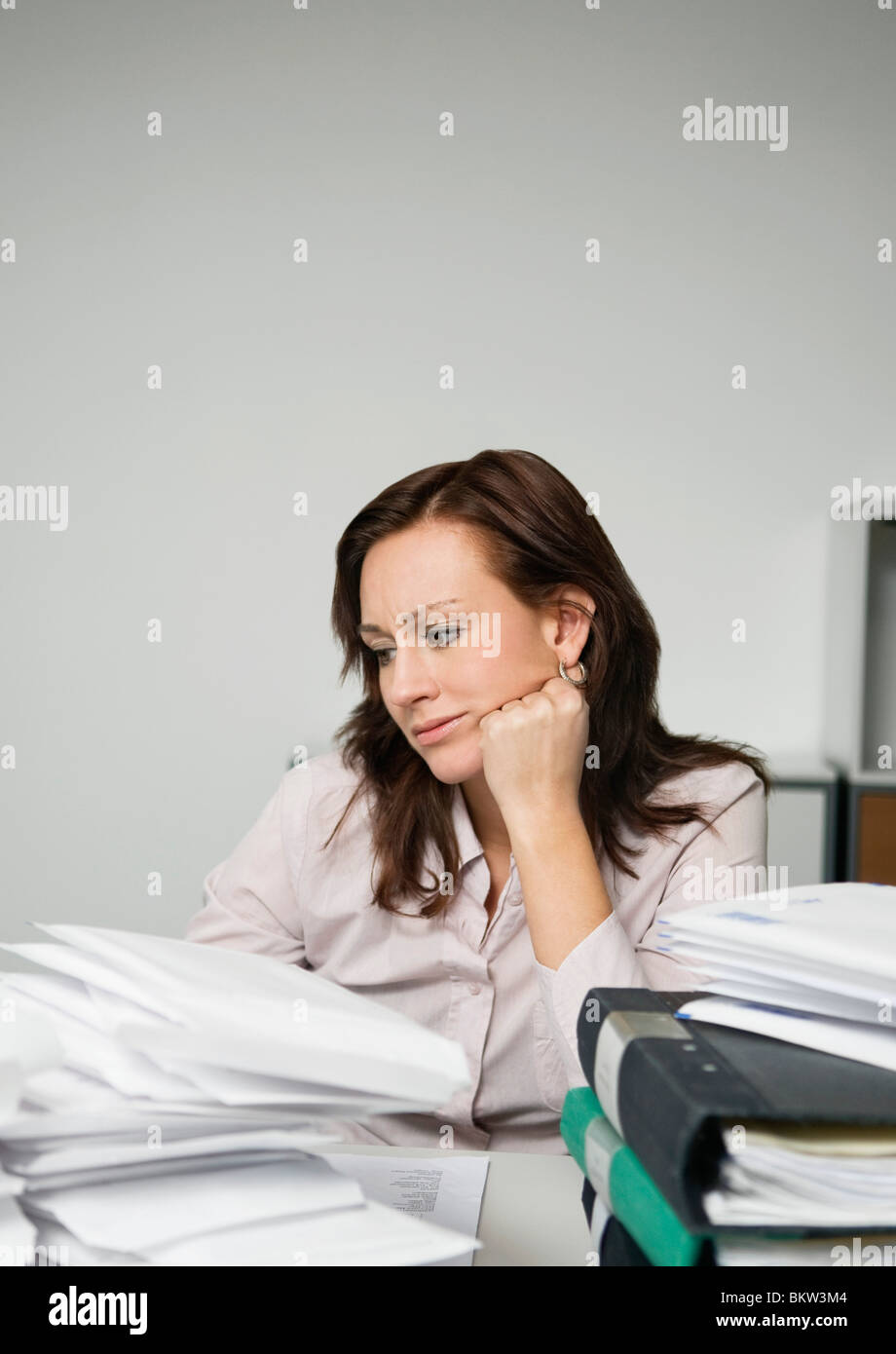 Troubled woman behind piles of paper - Stock Image