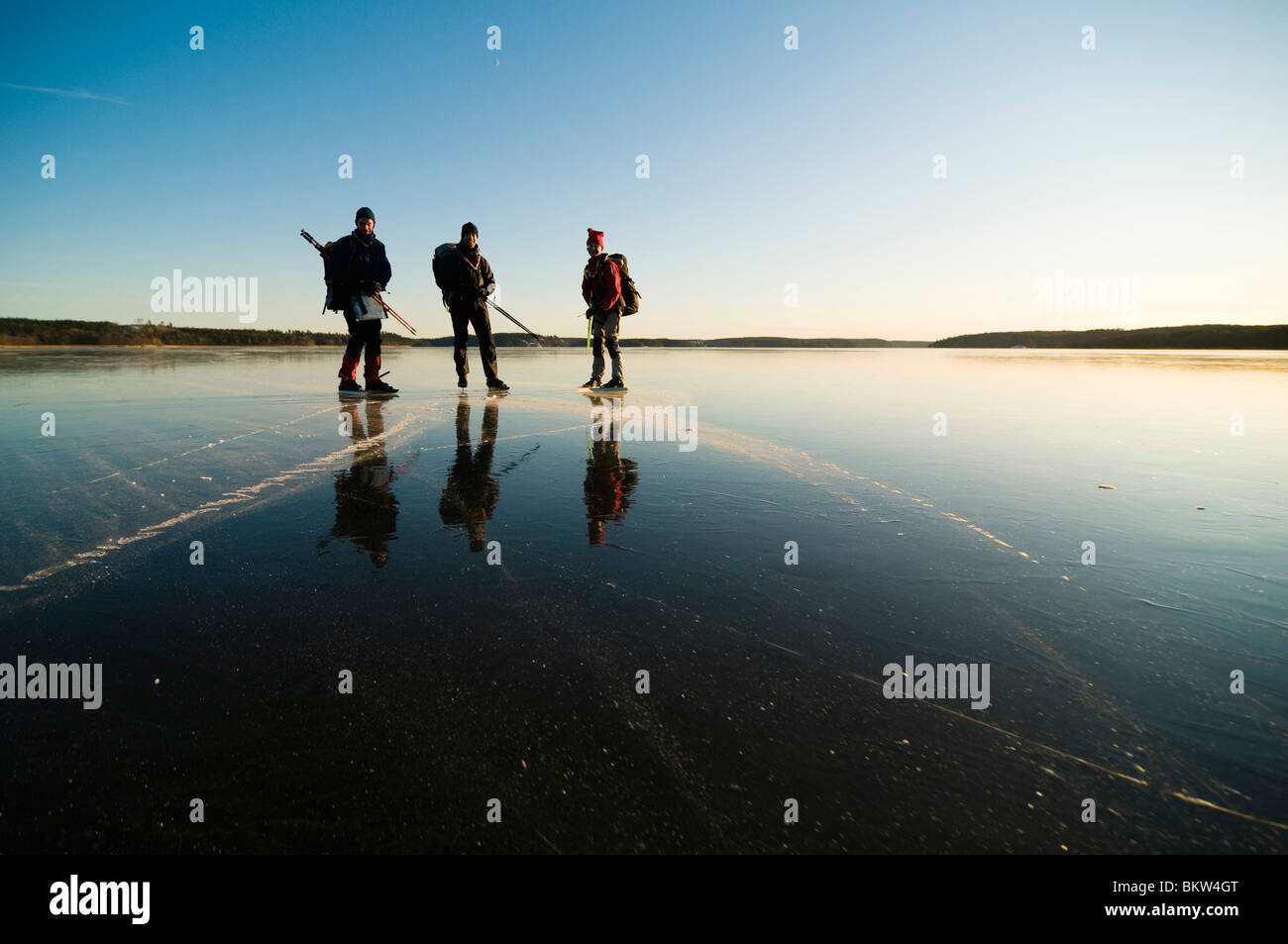Three long-distance skaters standing on ice - Stock Image