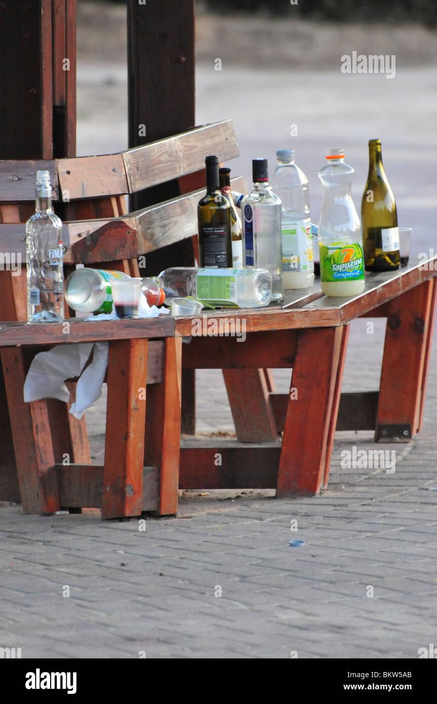 Empty alcohol bottles on a park bench. - Stock Image