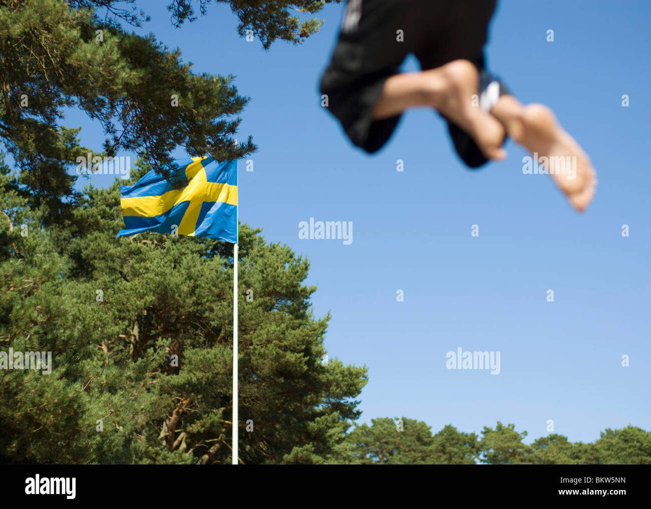 Swedish flag and a jumping child - Stock Image