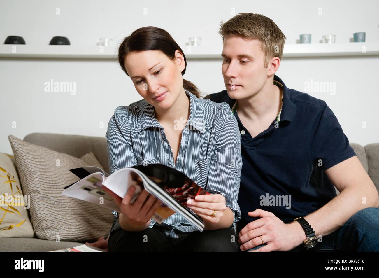 Couple reading magazine - Stock Image