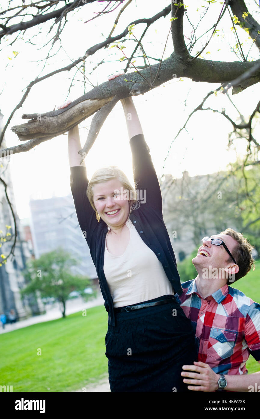 Woman playing in tree - Stock Image