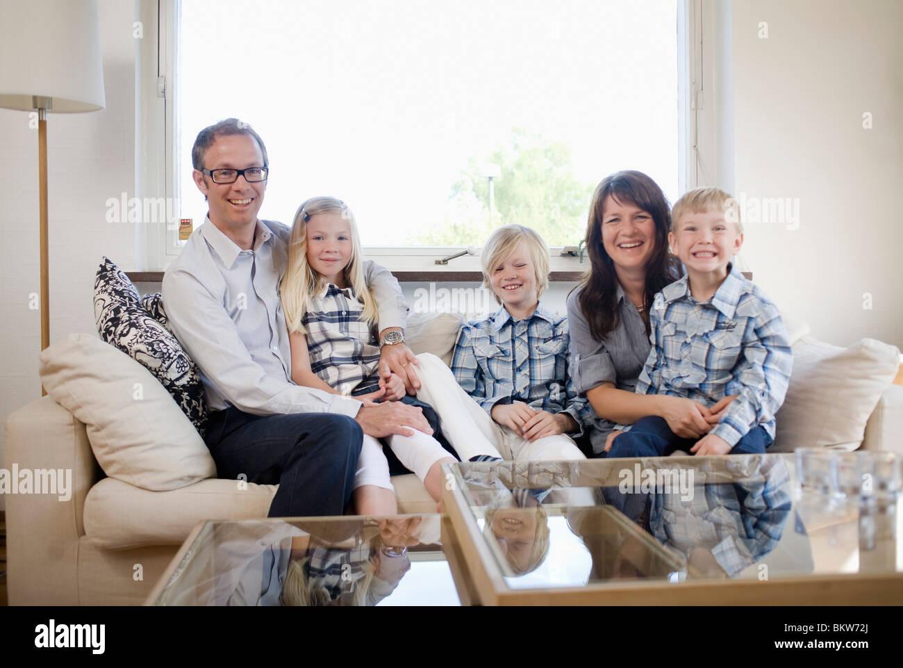Happy family in livingroom - Stock Image