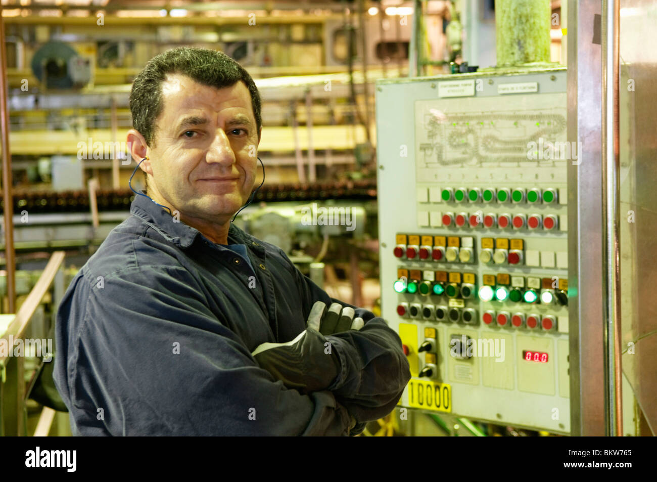 Man standing by control panel - Stock Image