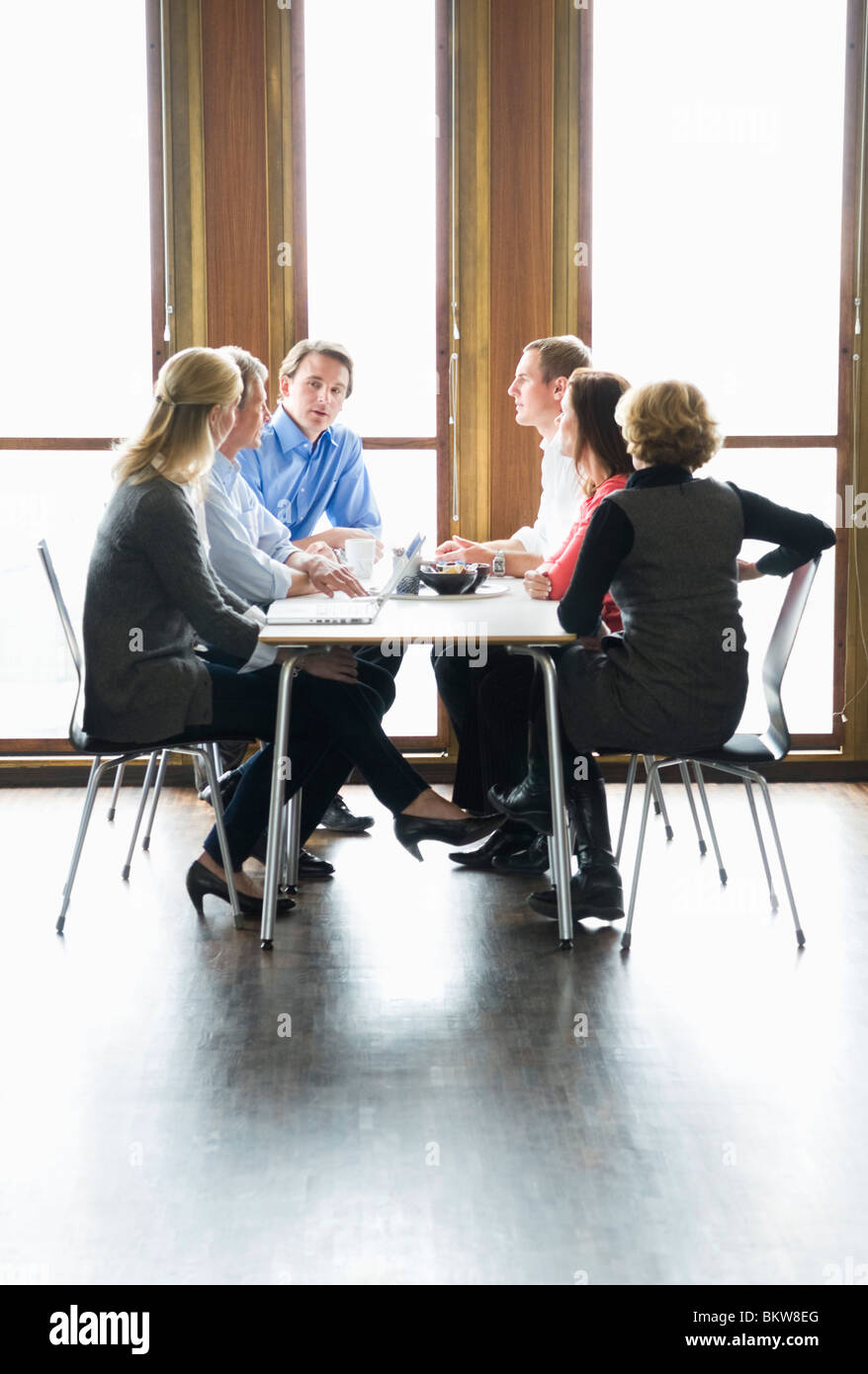Six people sitting by table talking - Stock Image
