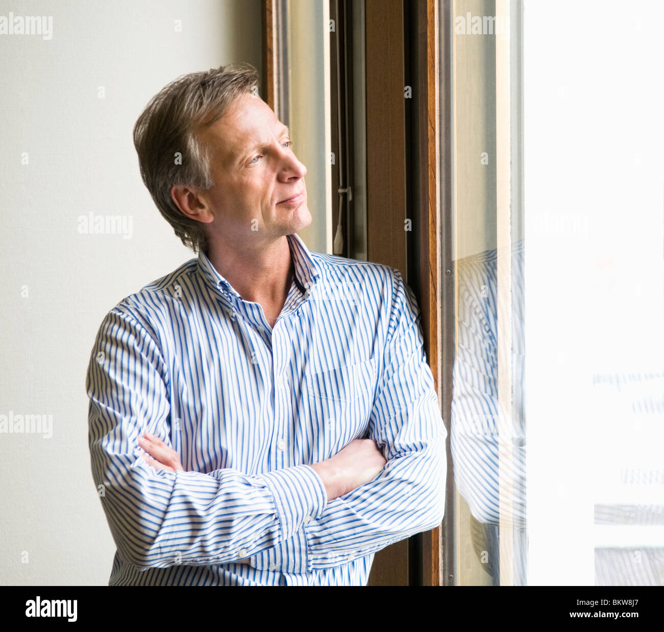 Businessman looking out through the window - Stock Image