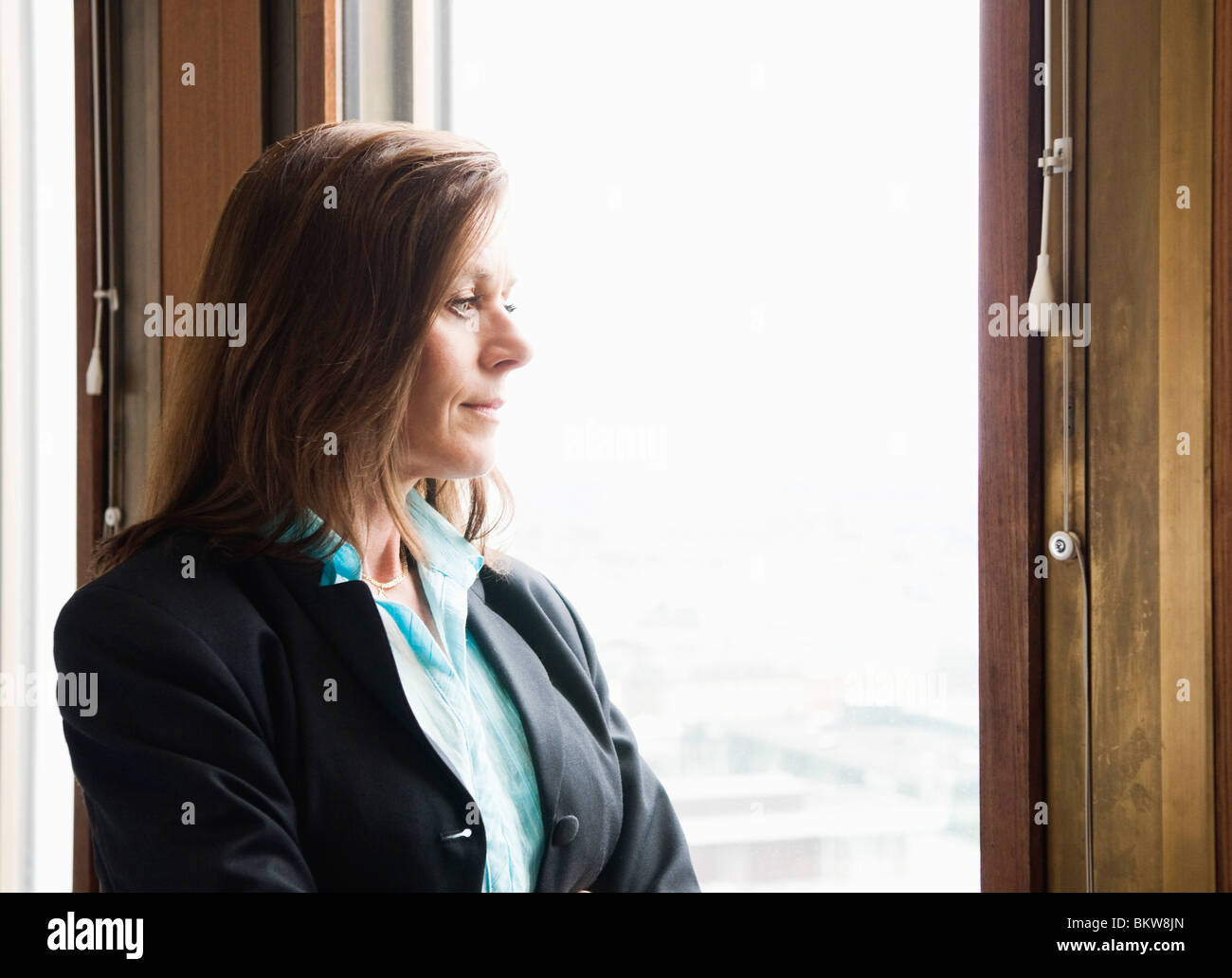 Businesswoman looking out through the window - Stock Image