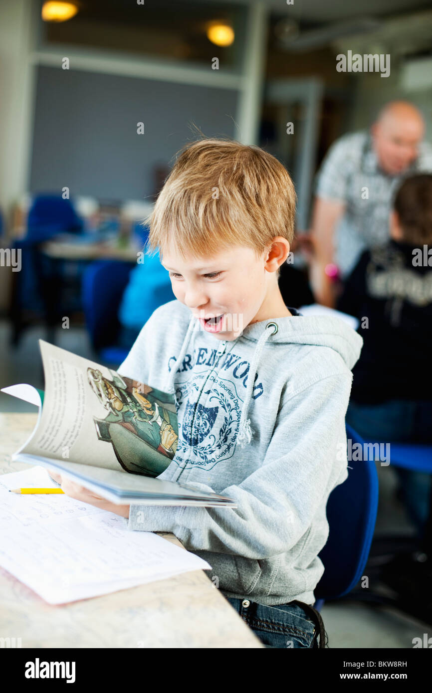 Boy reading textbook - Stock Image