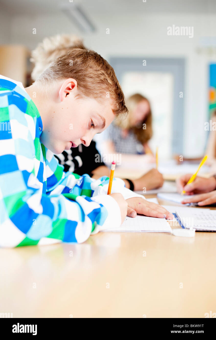 Concentrated boy writing in class - Stock Image