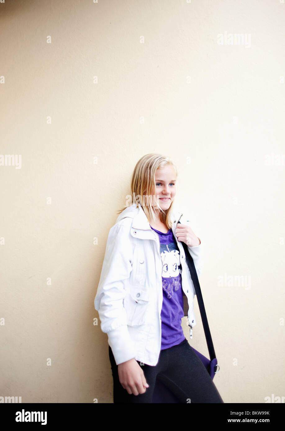 Girl standing against wall - Stock Image