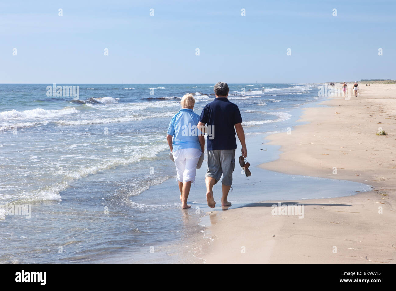 Two people walking in the water's edge - Stock Image