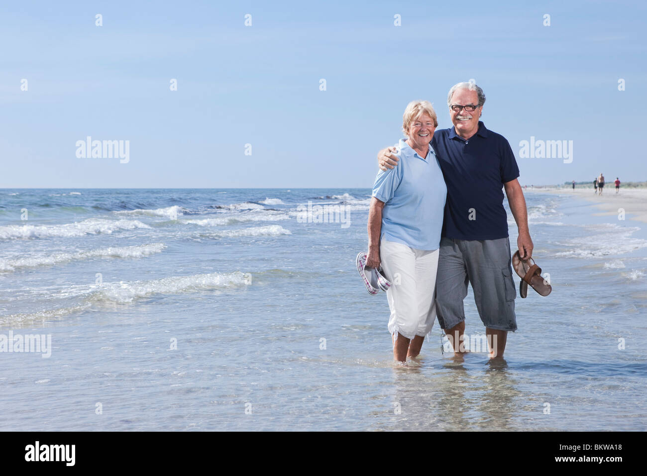 Two elderly people standing in the water's edge - Stock Image