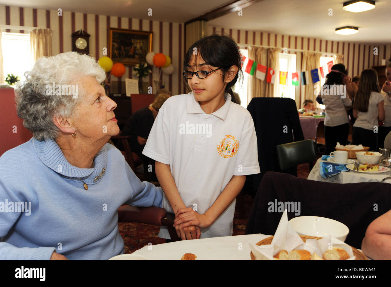 Primary School children meet elderly people at their residential home as part of a 'meet the neighbor' inter - Stock Image