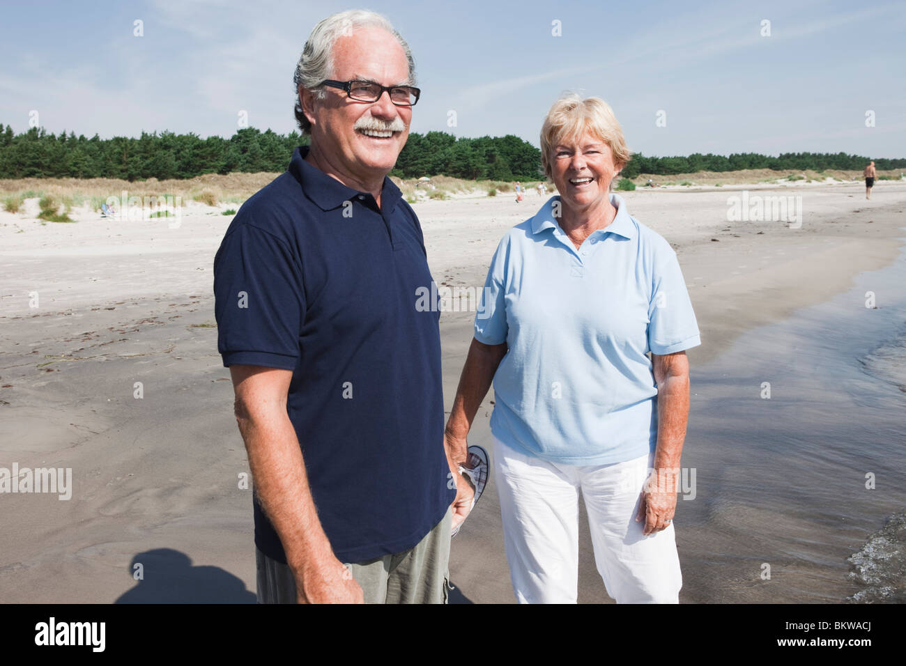 Couple standing in the water's edge - Stock Image