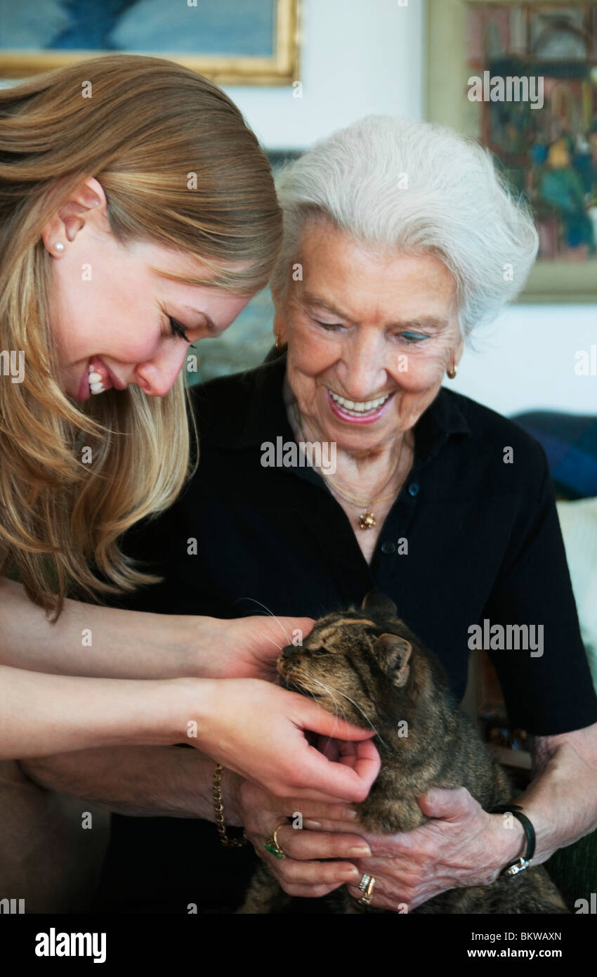 Two people cuddle with cat - Stock Image