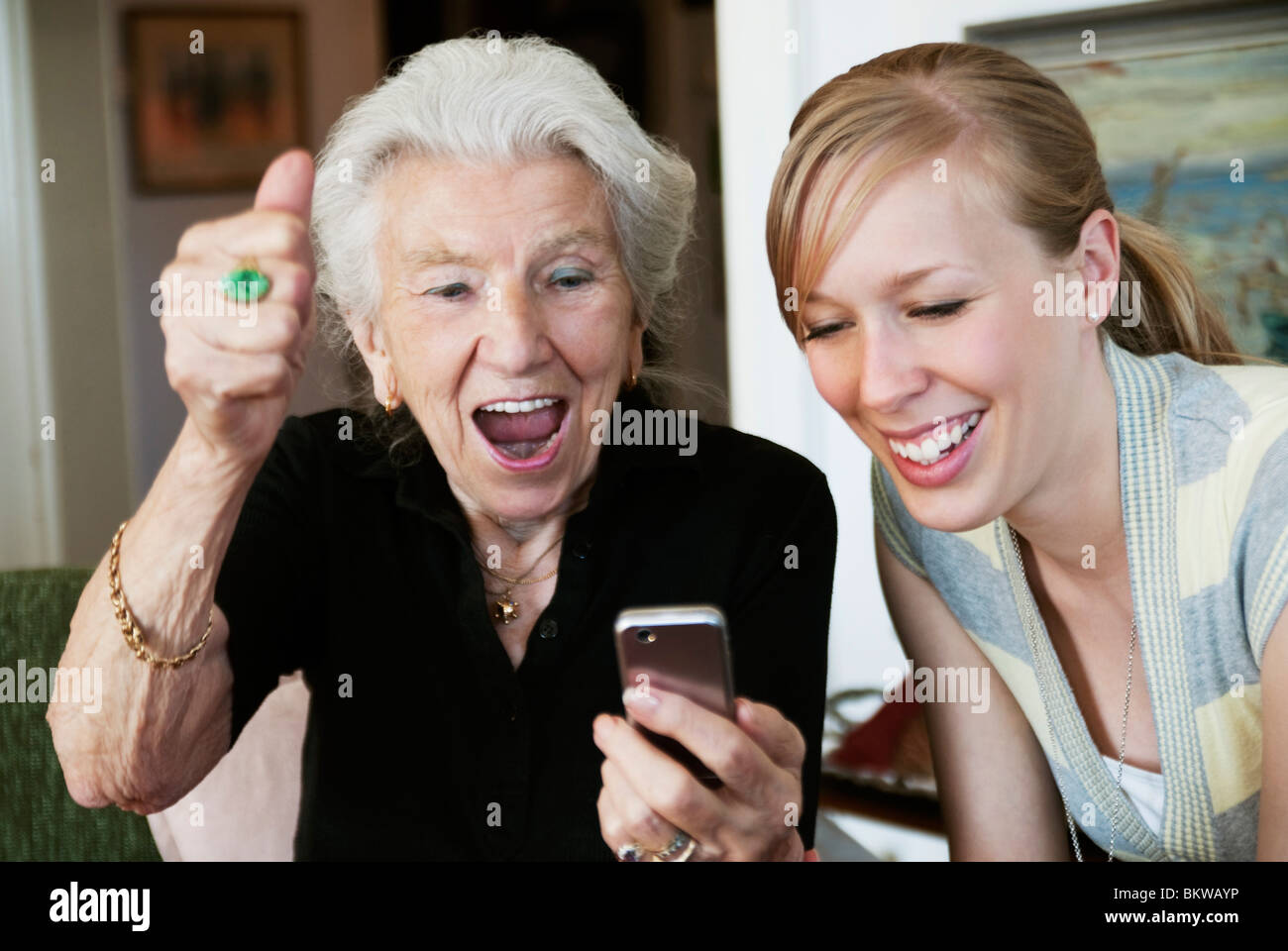 Elderly woman with cellphone beaming with joy - Stock Image
