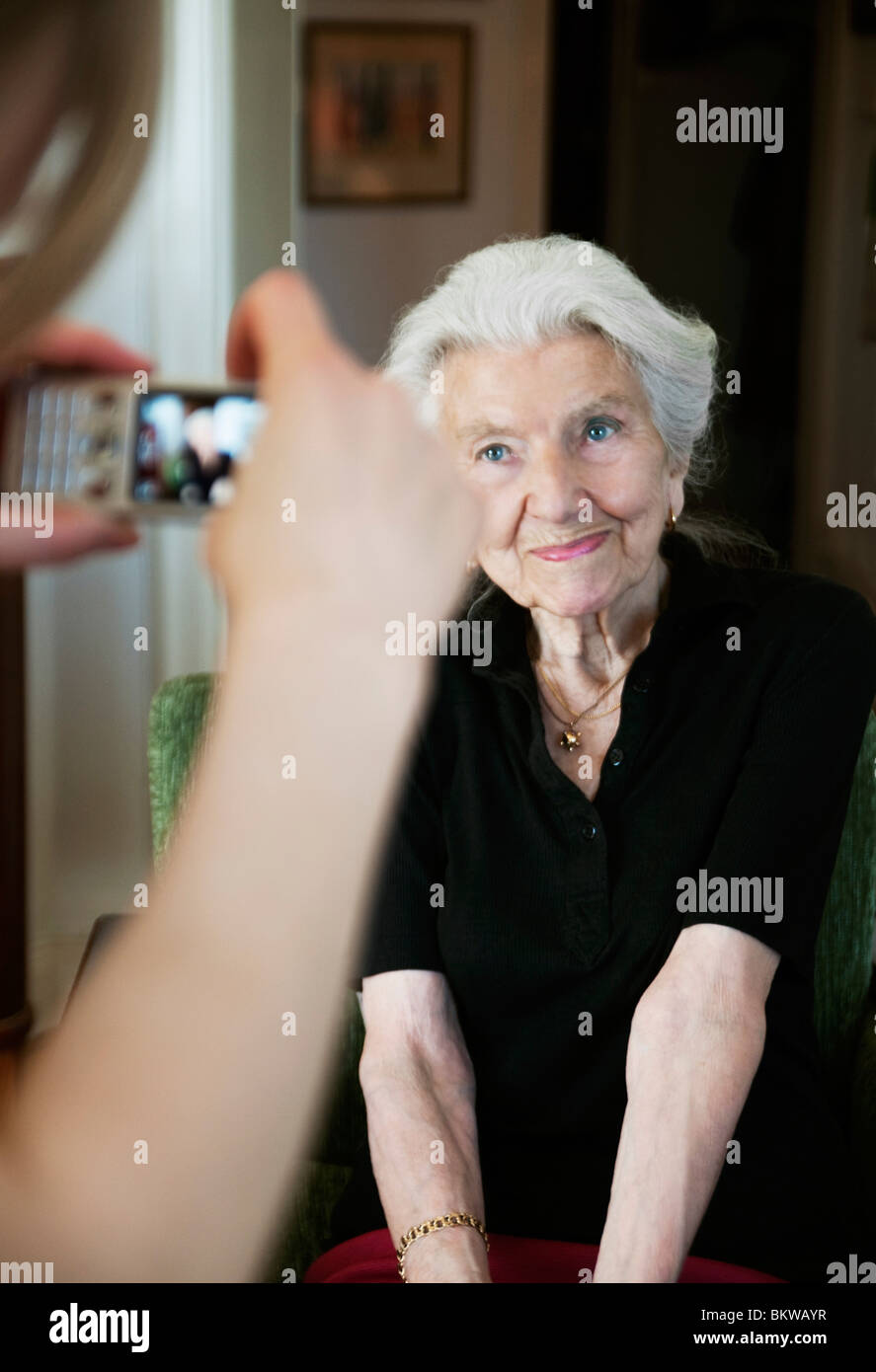 Young woman taking photo of an elderly lady with camera phone - Stock Image