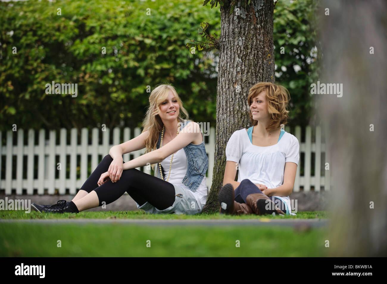 Two girls sitting under tree Stock Photo