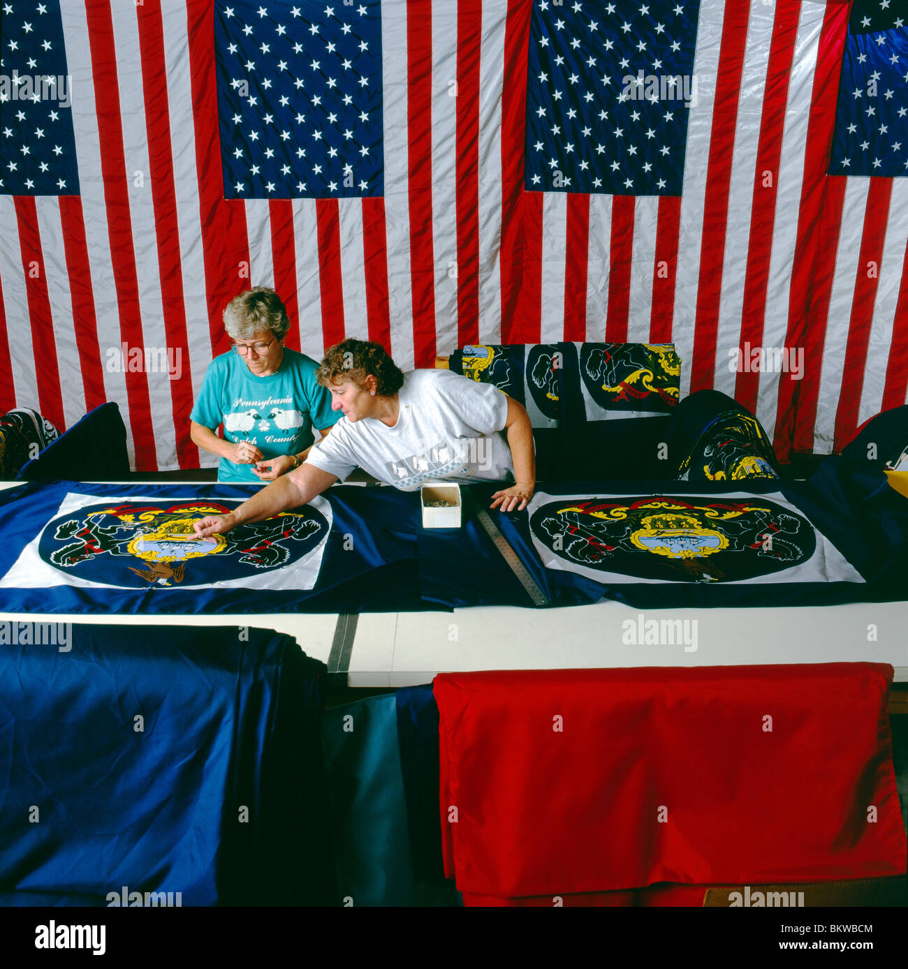 Two women work on Pennsylvania State flags at Valley Forge Flag Company, one of the largest flag manufacturers in - Stock Image
