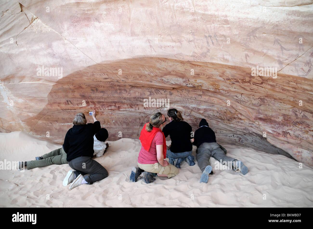 Travelers examining rock art at Mestekawi Cave, in the Gilf Kebir region of Egypt's Western Desert. - Stock Image