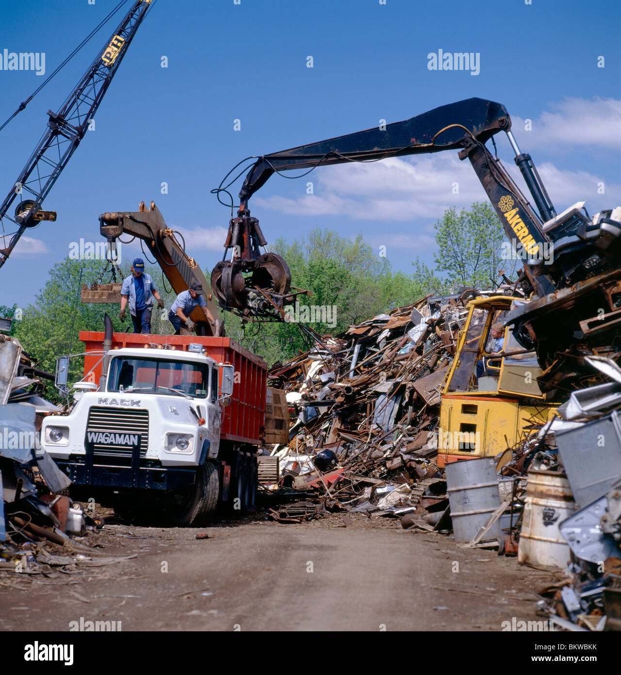 Heavy equipment loading scrap metal into a dump truck at a recycling center - Stock Image