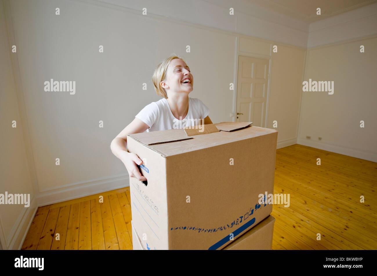 Woman lifting moving box - Stock Image