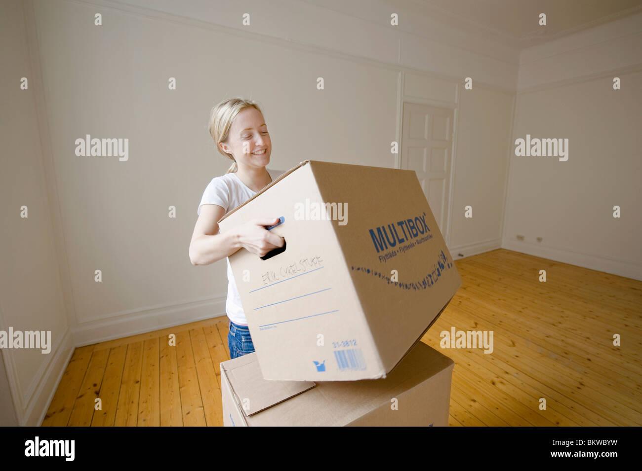 Girl lifting heavy moving box - Stock Image