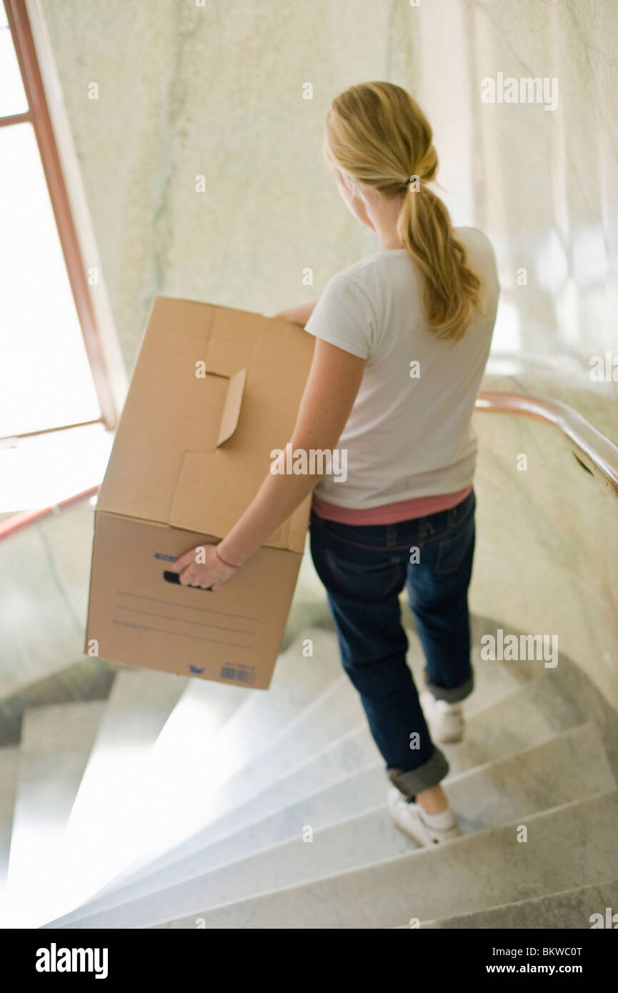 Woman carry moving box downstairs - Stock Image