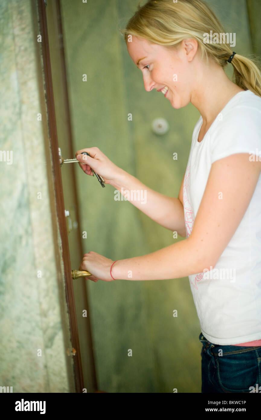 Woman unlocking the door - Stock Image