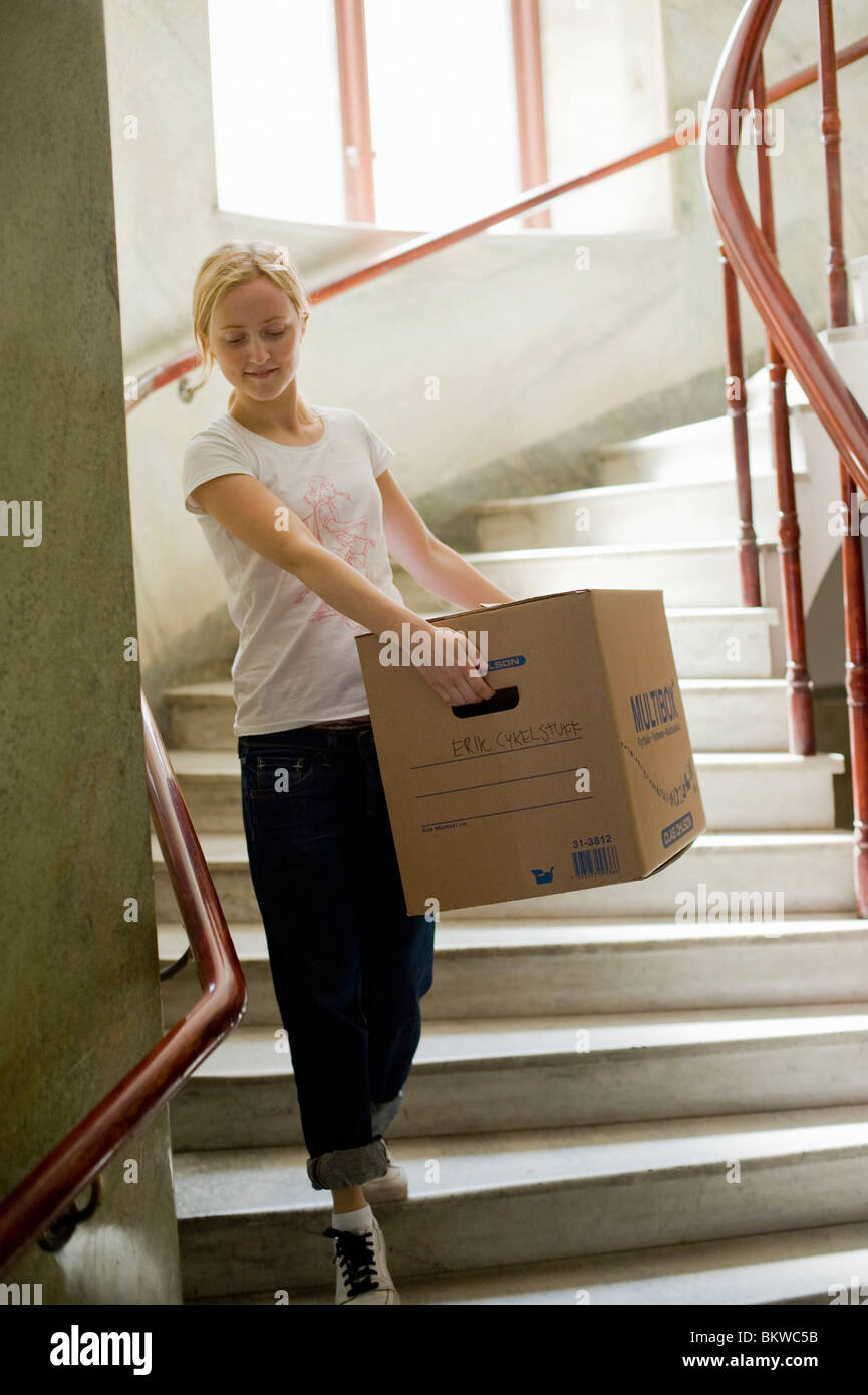 Woman in the stairs with moving box - Stock Image