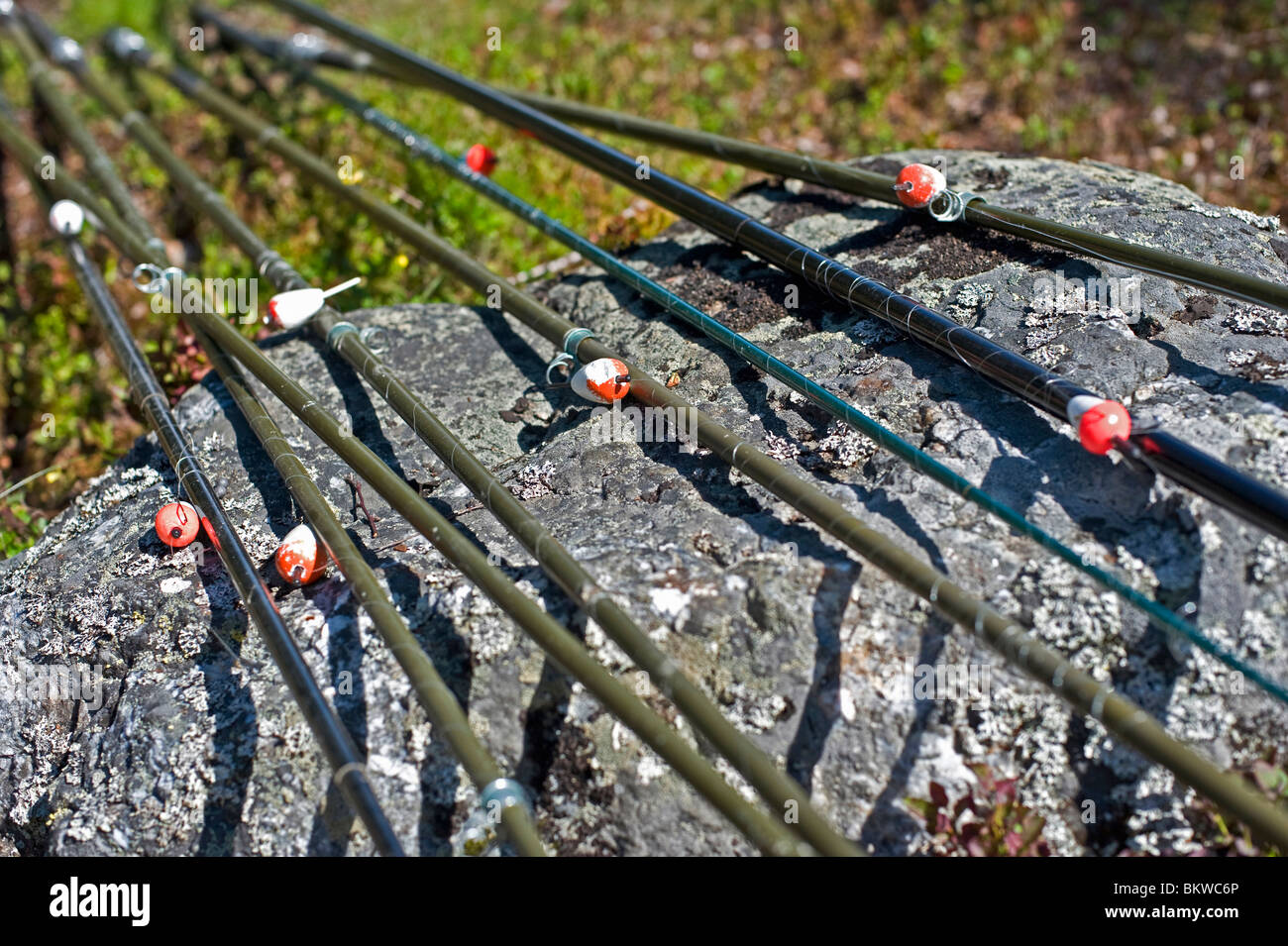 A number of fishingrods lying on rock - Stock Image
