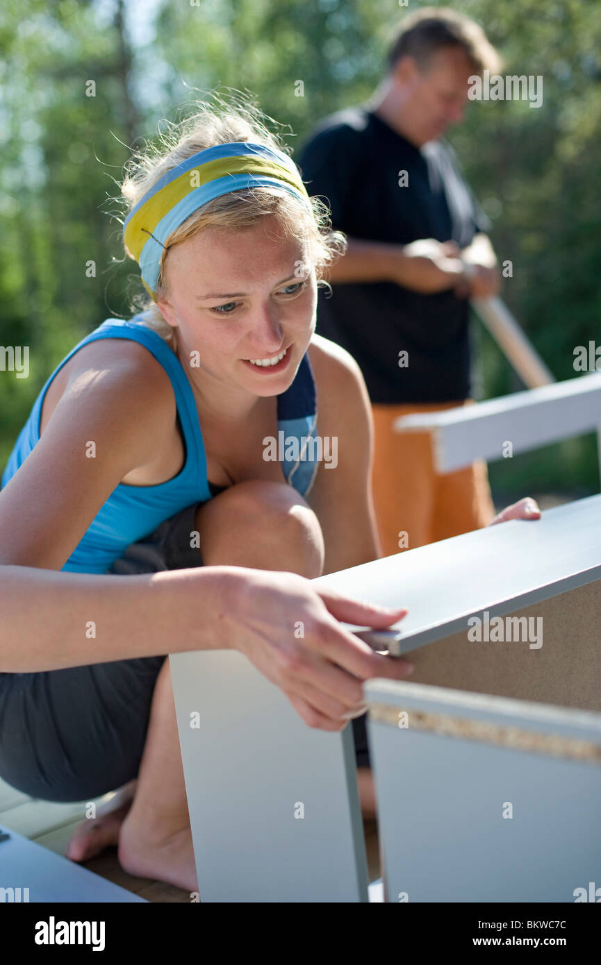 Concentrated woman mounting shelf - Stock Image