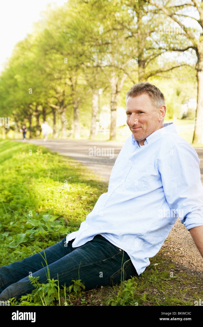 Man sitting by verge - Stock Image