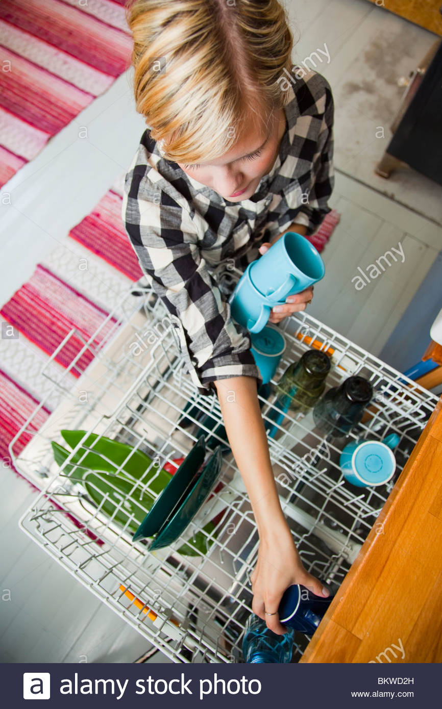 Gilr taking out the dishes - Stock Image