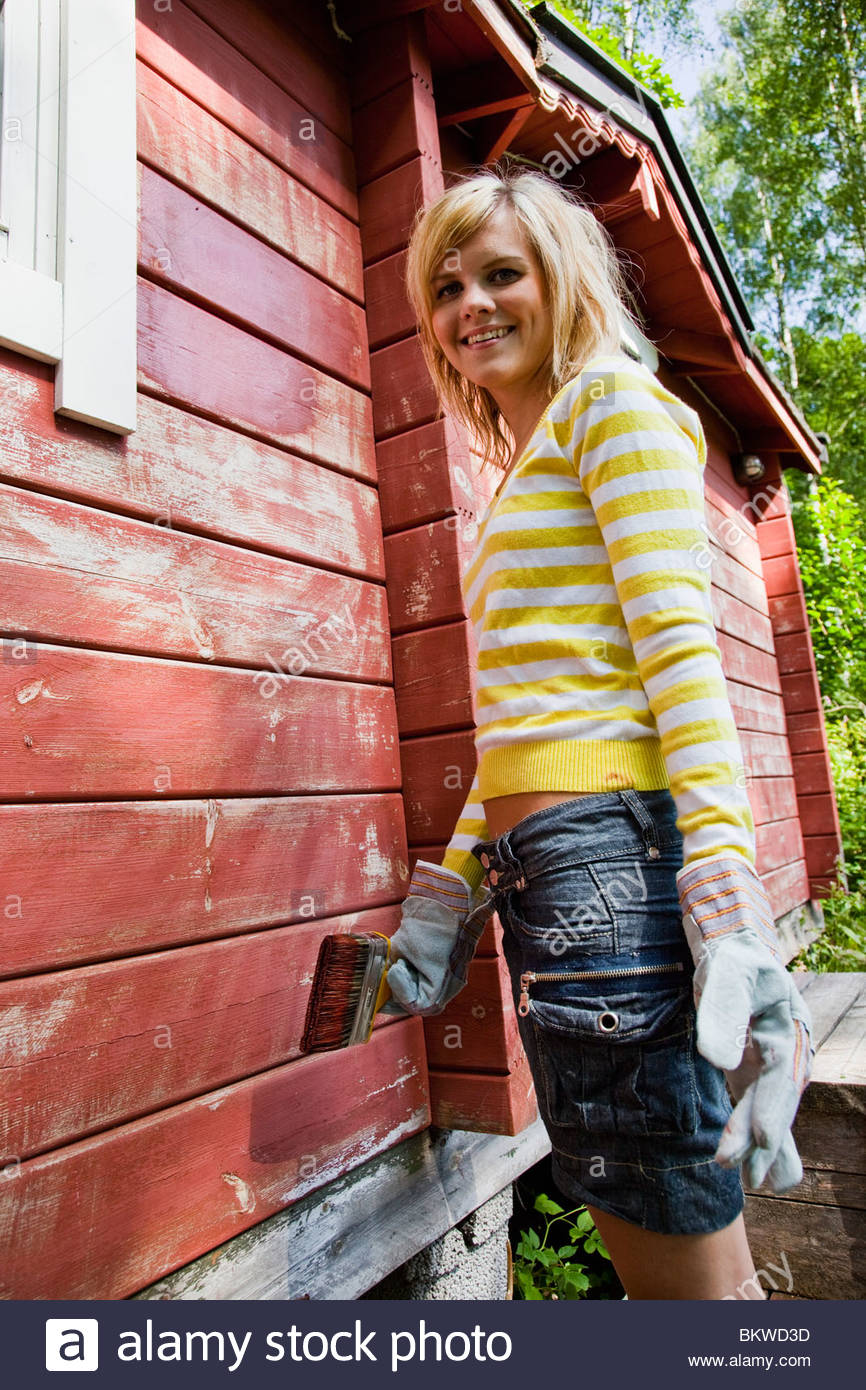 Girl painting house - Stock Image