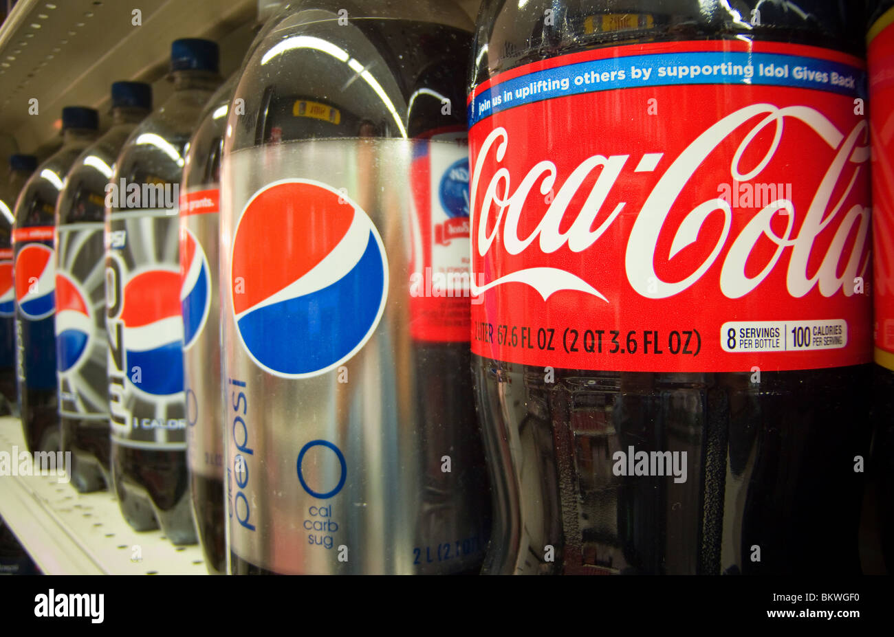 Bottles of Pepsi-Cola and Coca-Cola on a supermarket shelf in New York - Stock Image