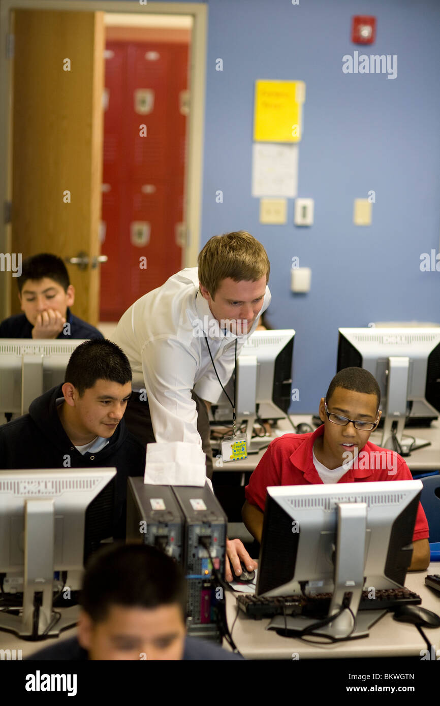 Teacher assists high school students in computer lab at charter school Peak Preparatory Academy in Dallas, Texas, - Stock Image