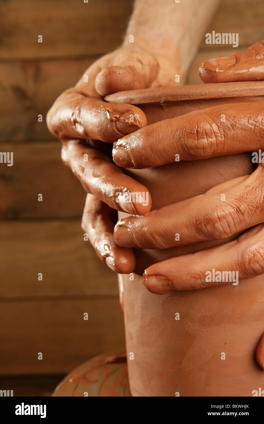 pottery craftmanship red clay potter hands work finger closeup - Stock Image