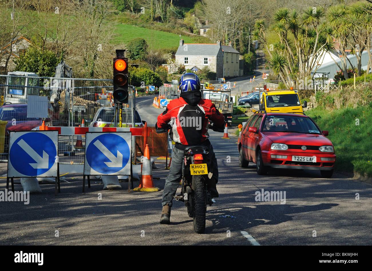 a motorbike waiting at roadworks traffic control lights, cornwall, uk - Stock Image