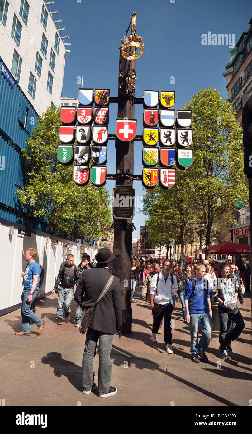 A tourist looking at the emblems of all the Swiss cantons, Swiss Court, The Swiss Centre, Leicester Square, London, - Stock Image