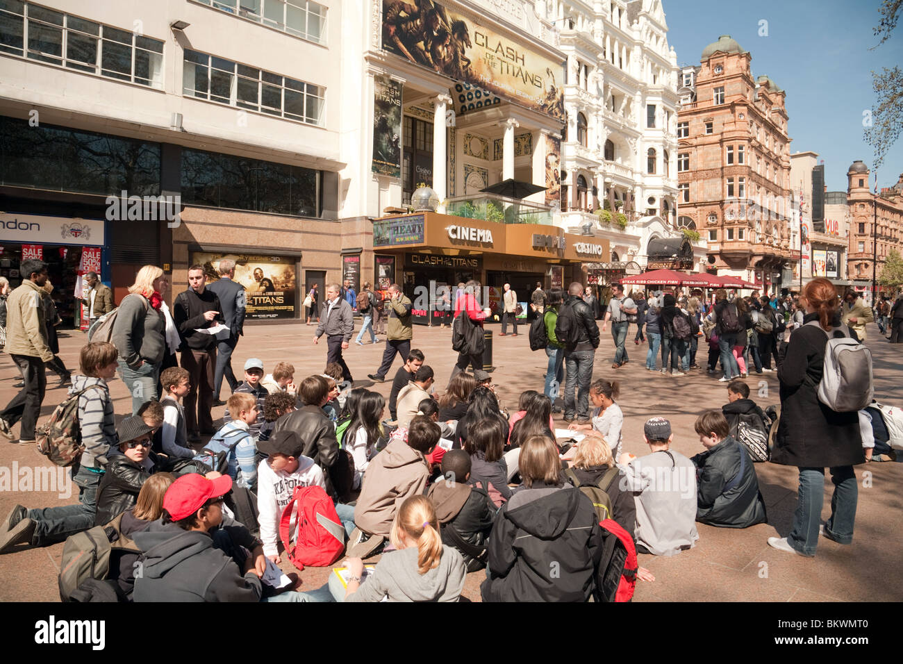Teenagers sitting in the sunshine, Leicester Square, London UK - Stock Image
