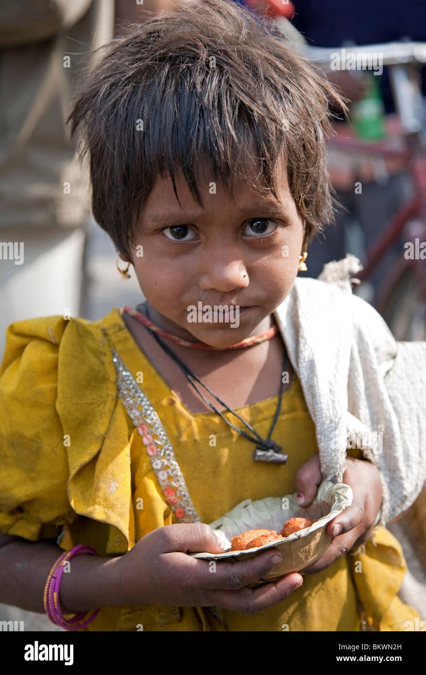 Little beggar eating pakoras. Jaipur. Rajasthan. India - Stock Image