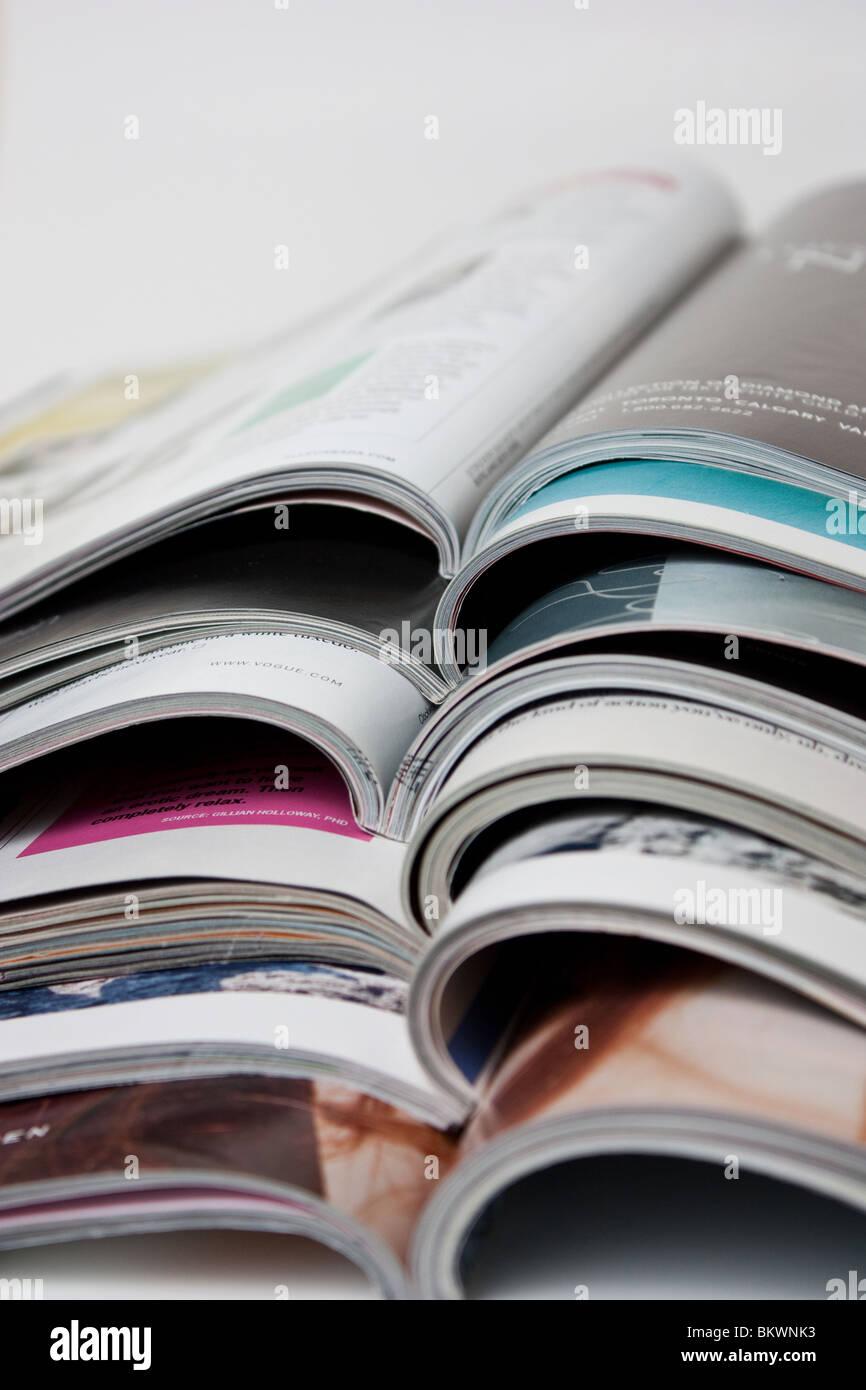 opened magazines on a pile magazine women spread pile magazines vogue fashion - Stock Image