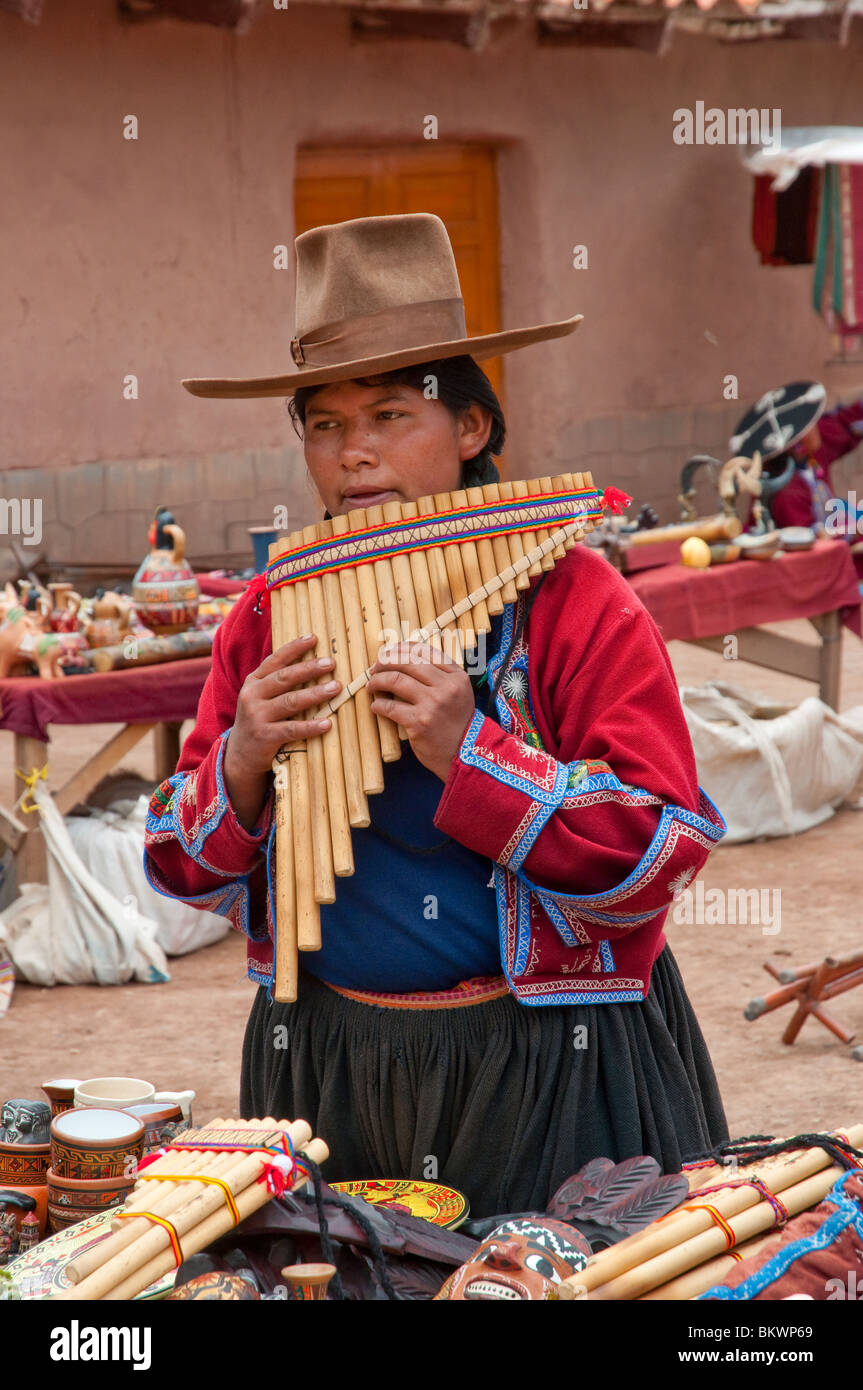 A peruvian woman in traditional dress plays the pan pipe in the plaza in Racchi, Peru, South America. - Stock Image