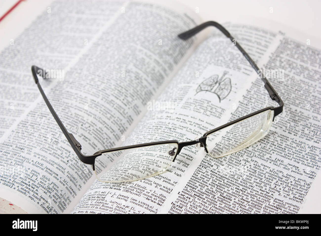 black framed eyeglasses on book - Stock Image