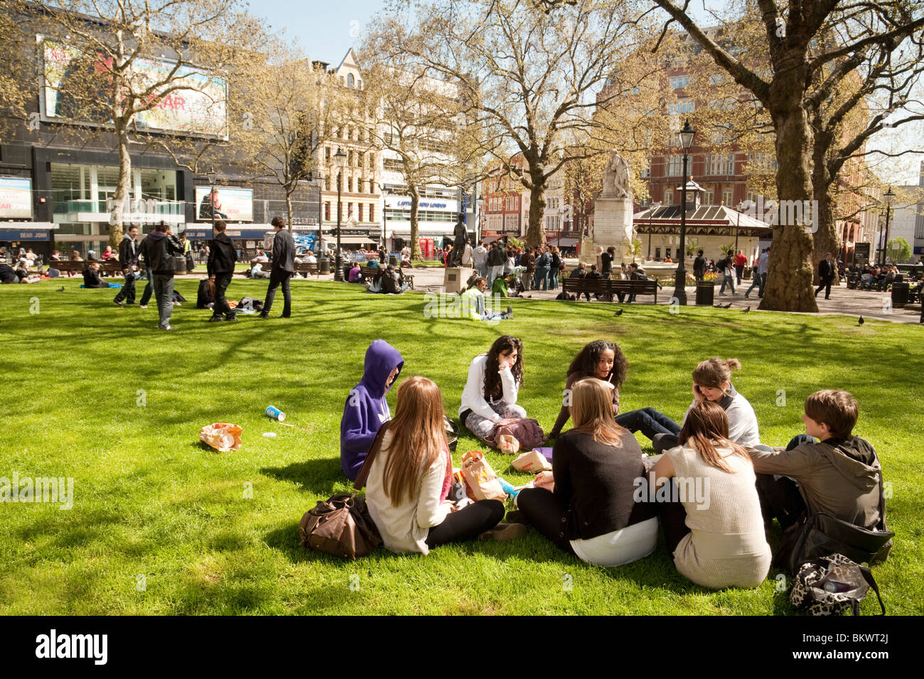 A group of teenagers sitting on the grass in the summer sunshine, Leicester Square, London UK - Stock Image